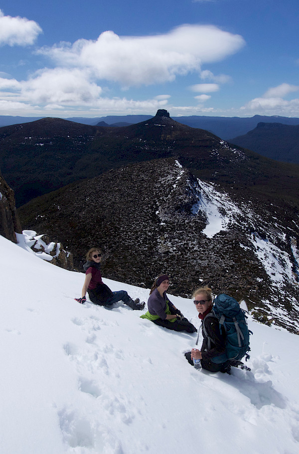 Three walkers sitting in the snow on the slopes of Mt Ossa