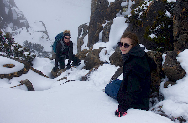 Walkers on a snow-covered boulder scramble