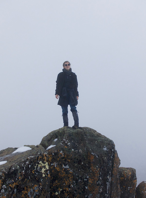 Walker standing on top of a rock, in bad weather