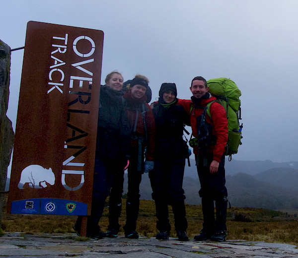 Walkers at the end of the overland track near the track sign