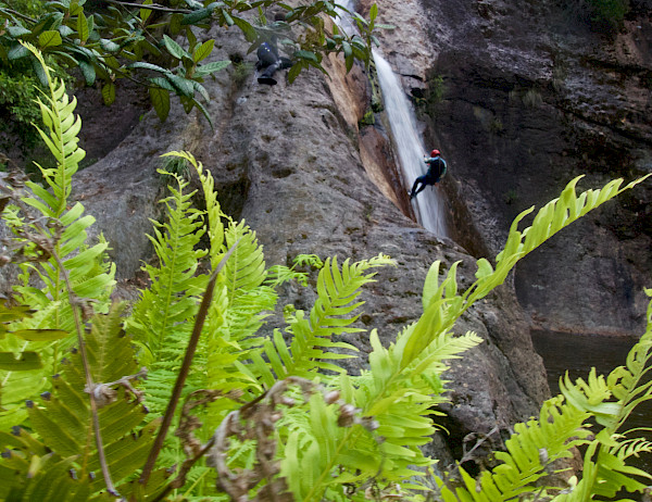 Person in the distance abseiling down a waterfall