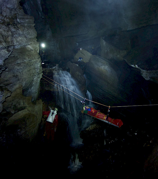 Stretcher suspended by ropes in the cave