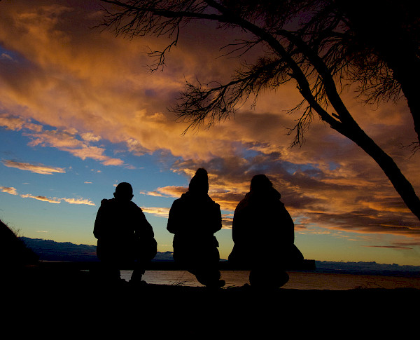 Three people sitting in silhouette, in the sunset