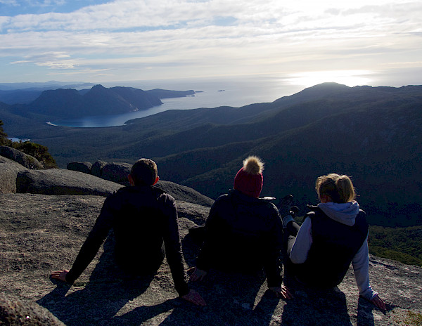 Three people sitting on a mountain looking away from the camera towards the coast